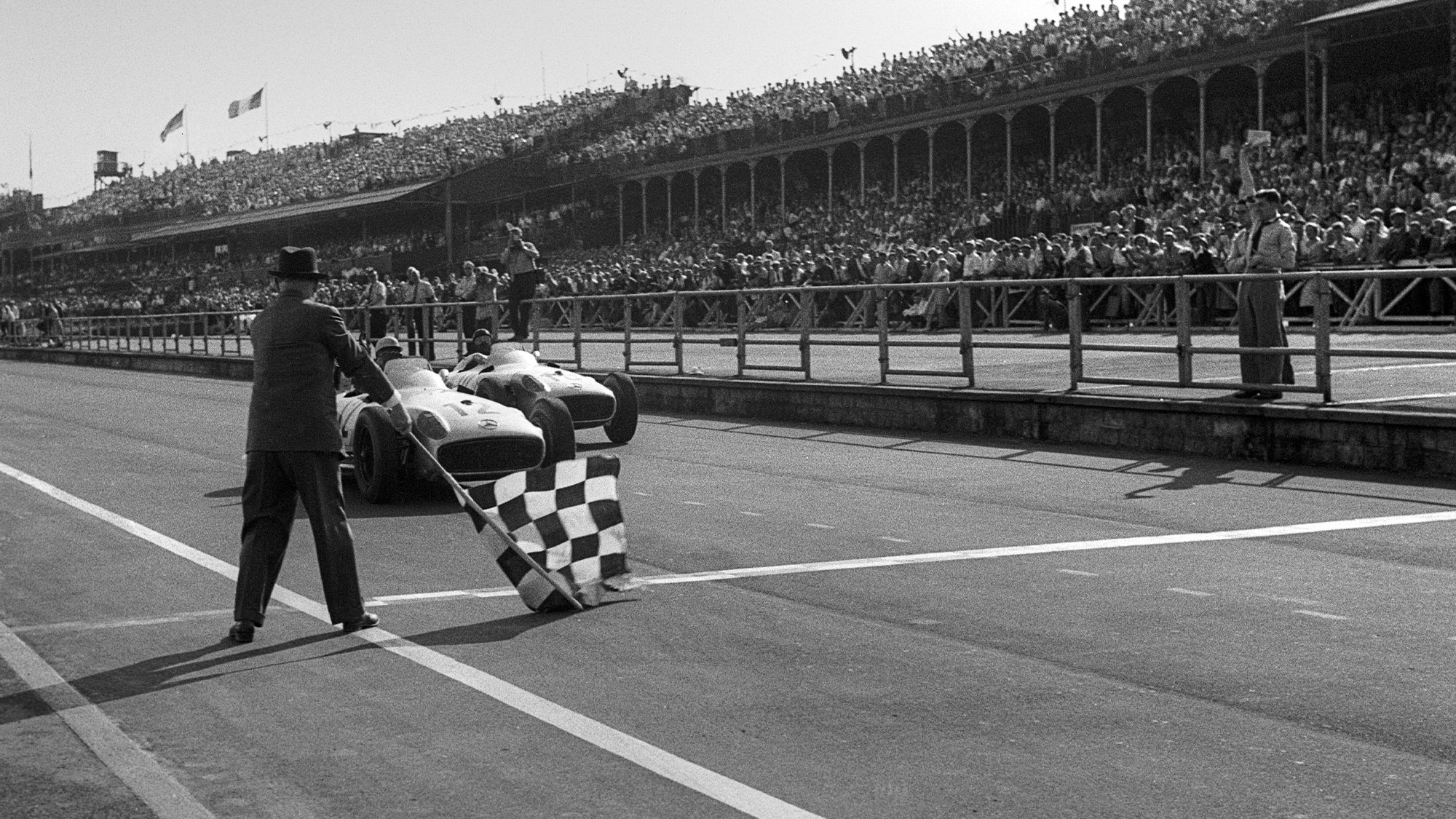 Stirling Moss beats Juan Manuel Fangio by half a car length at the finish line of the 1955 British Grand Prix at Aintree