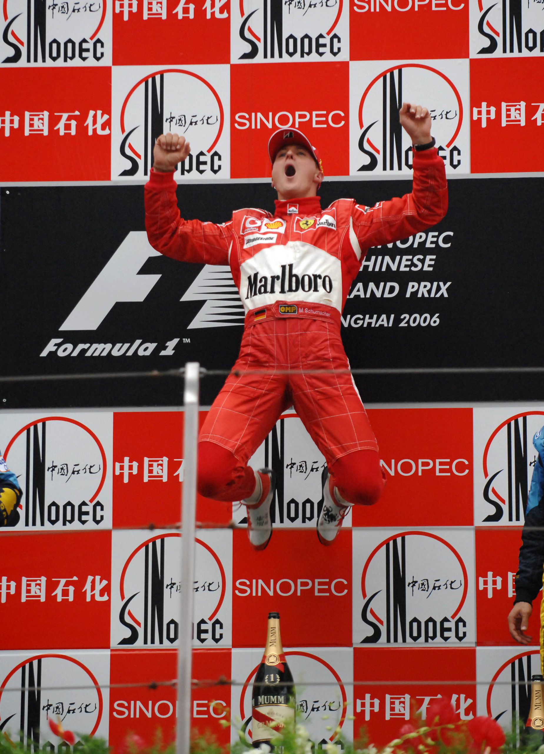 Michael-Schumacher-leaps-on-the-podium-at-the-2006-Chinese-Grand-Prix-after-his-final-91st-F1-win