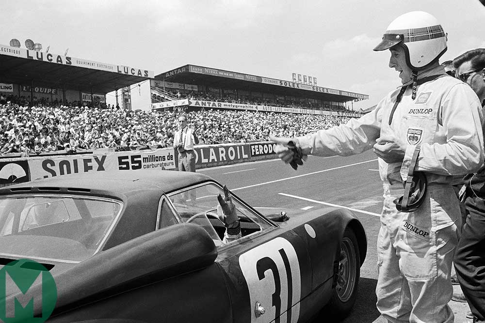 Graham Hill gestures at Jackie Stewart as he leaves the pits