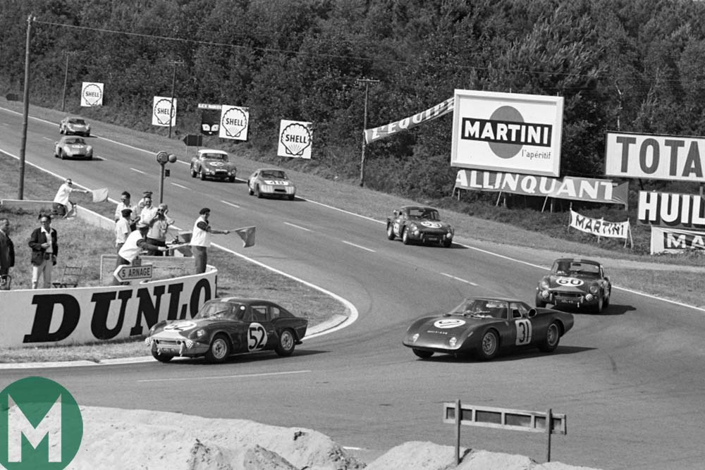 A Triumph Spitfire leads Jackie Stewart and Graham Hill's Rover-BRM at the 1965 Le Mans 24 hours