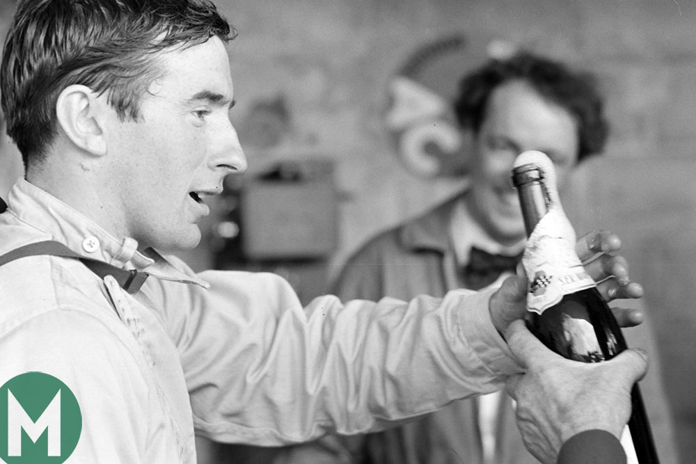 Jackie Stewart celebrates tenth position at the 1965 Le Mans 24 Hours with champagne