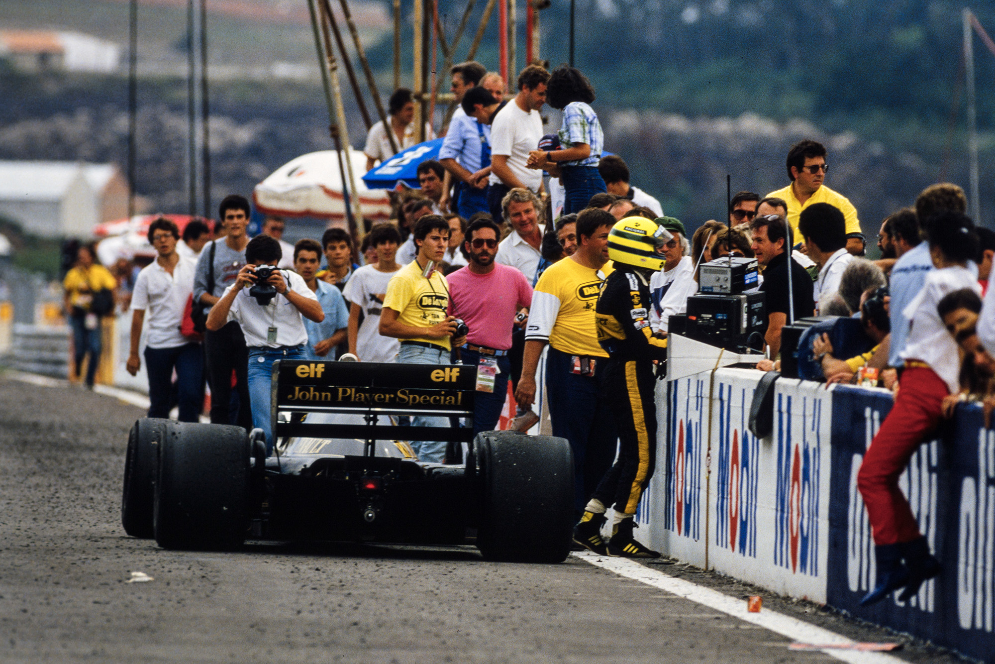 Ayrton Senna talks to his pit crew at the side of the track after running out of fuel in the 1986 F1 Portuguese Grand Prix