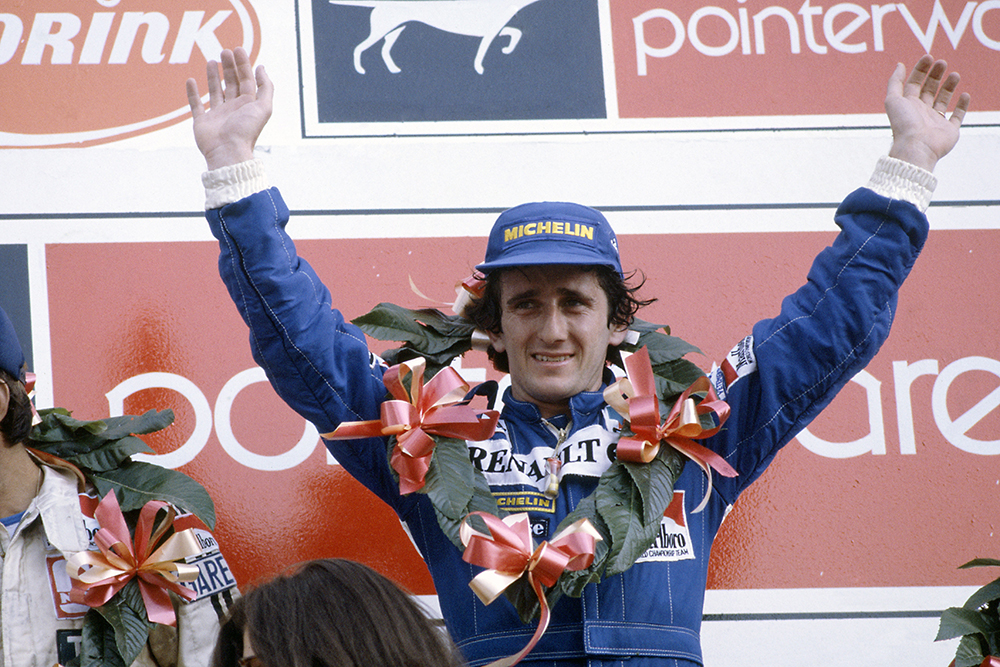 Alain Prost celebrates his win on the podium.
