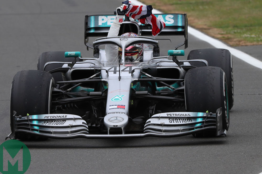 Lewis Hamilton waves a Union Jack on his slowing down lap after winning the 2019 British Grand Prix