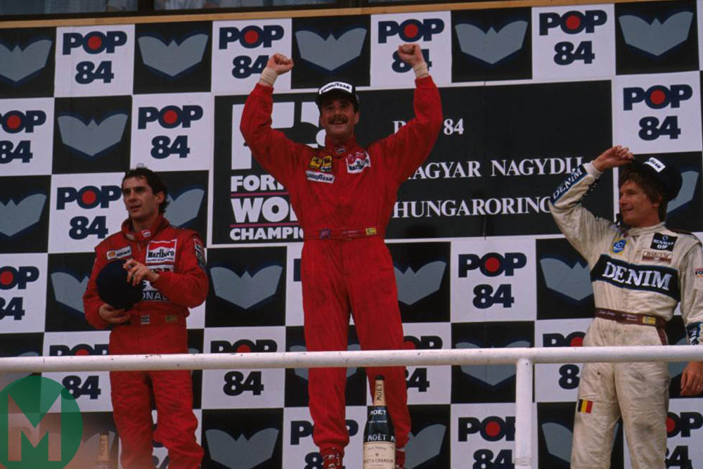 Mansell celebrates on the podium, flanked by Ayrton Senna and Thierry Boutsen