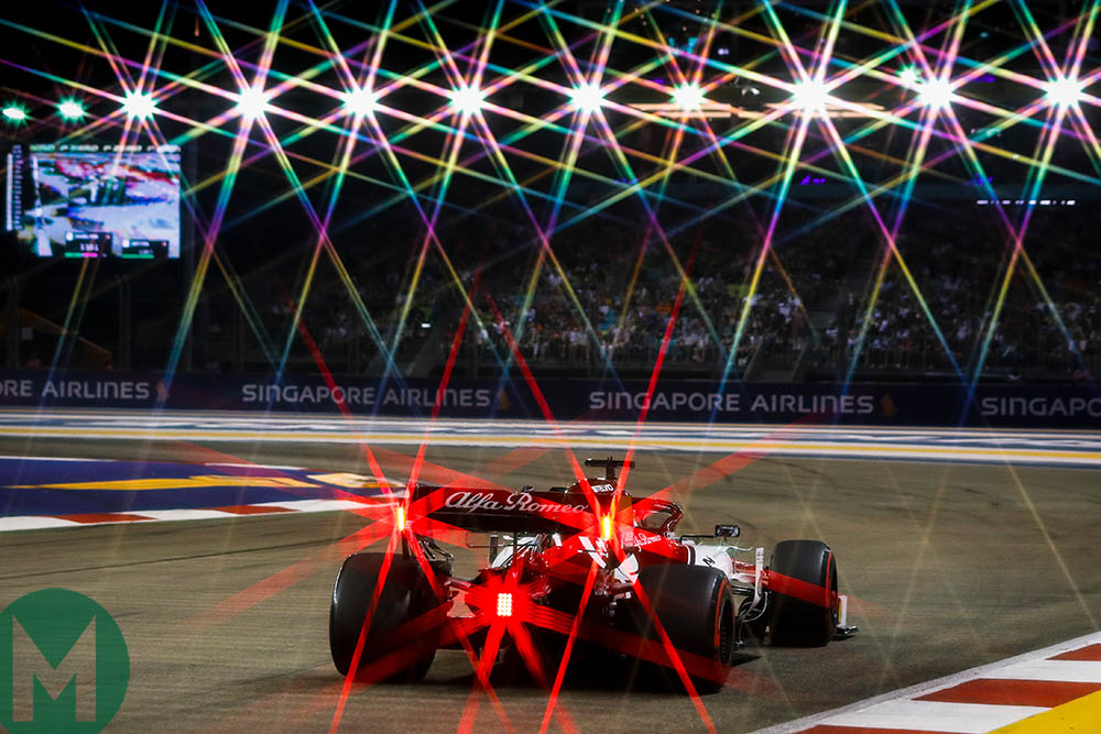 The red rear lights of an Alfa Romeo combine with the circuit's floodlights at the 2019 F1 Singapore Grand Prix