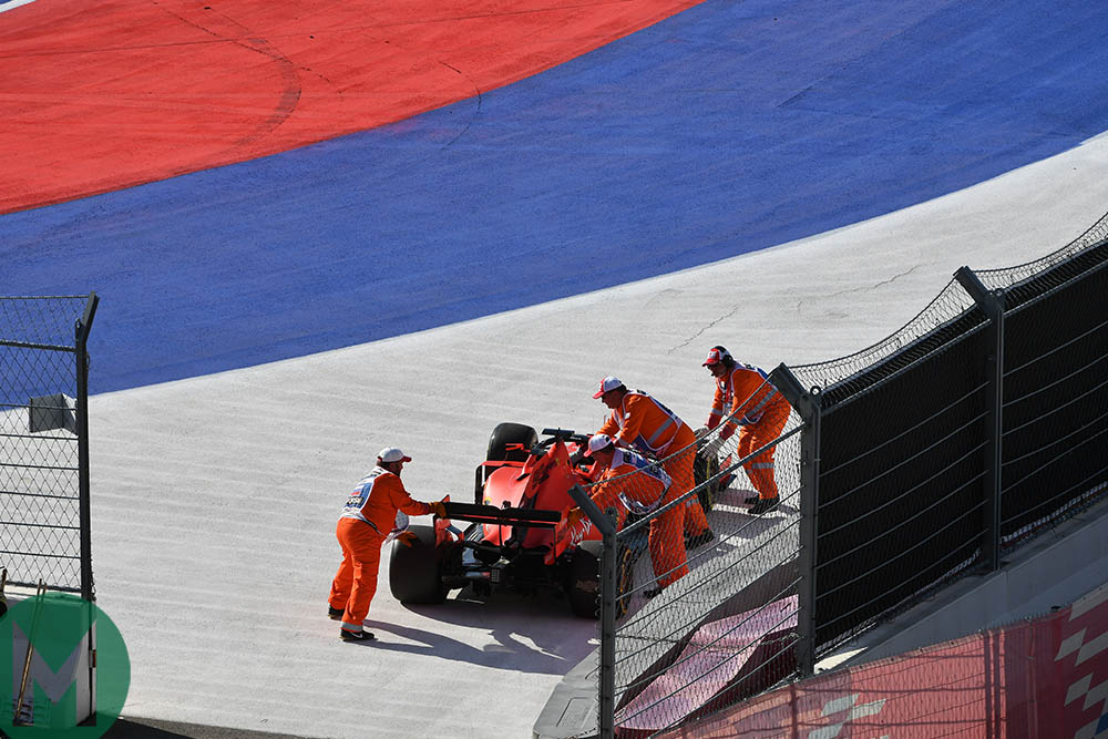 Marshals wheel Sebastian Vettel's car away after he retired from the 2019 F1 Russian Grand Prix