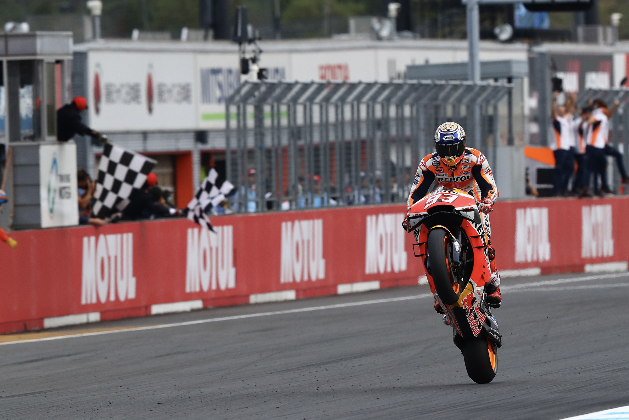 Marc Marquez takes the chequered flag with a wheelie to win the 2019 MotoGP Grand Prix of Japan