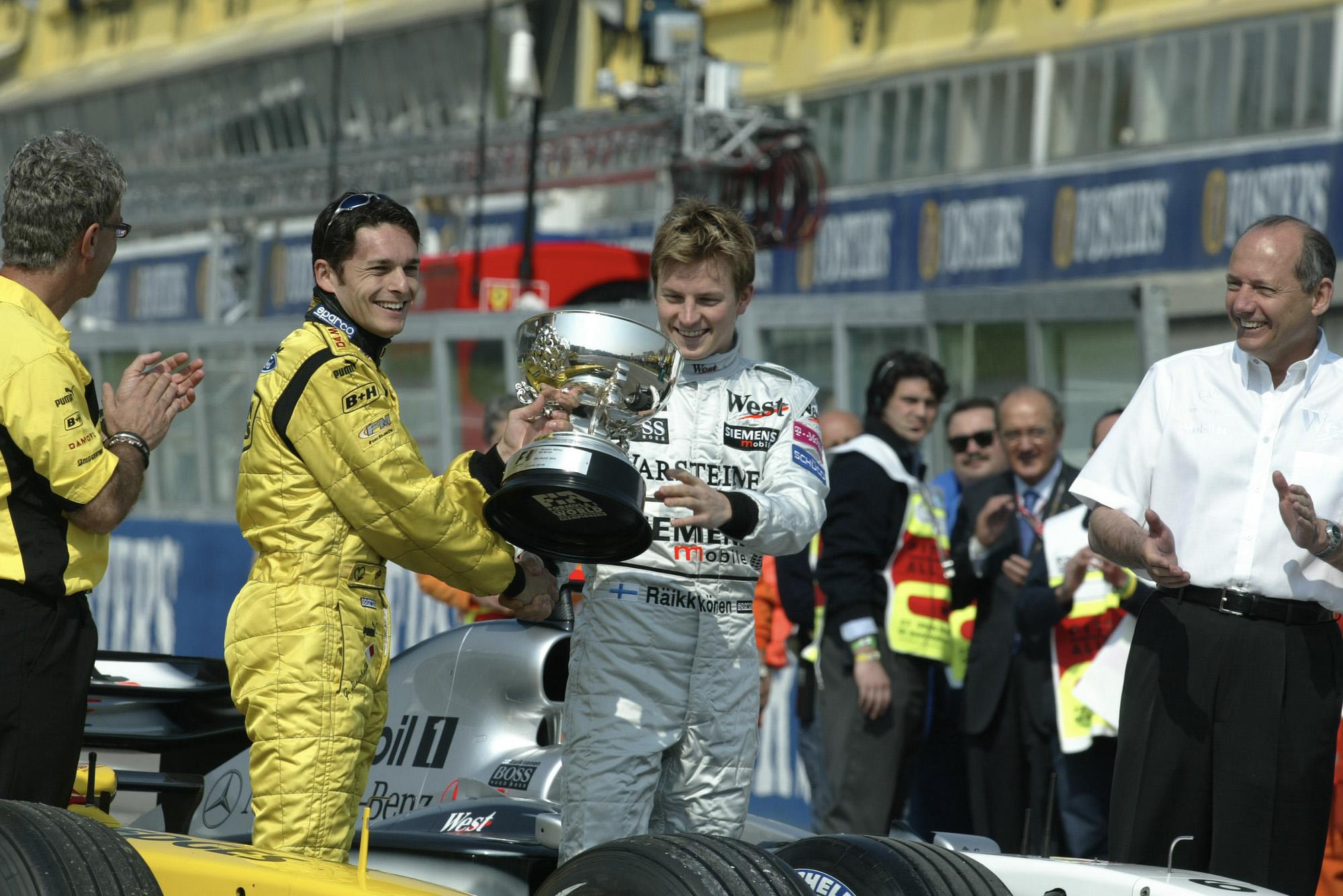 Kimi Raikkonen hands the winning trophy for the 2003 F1 Brazilian Grand Prix to Giancarlo Fisichella