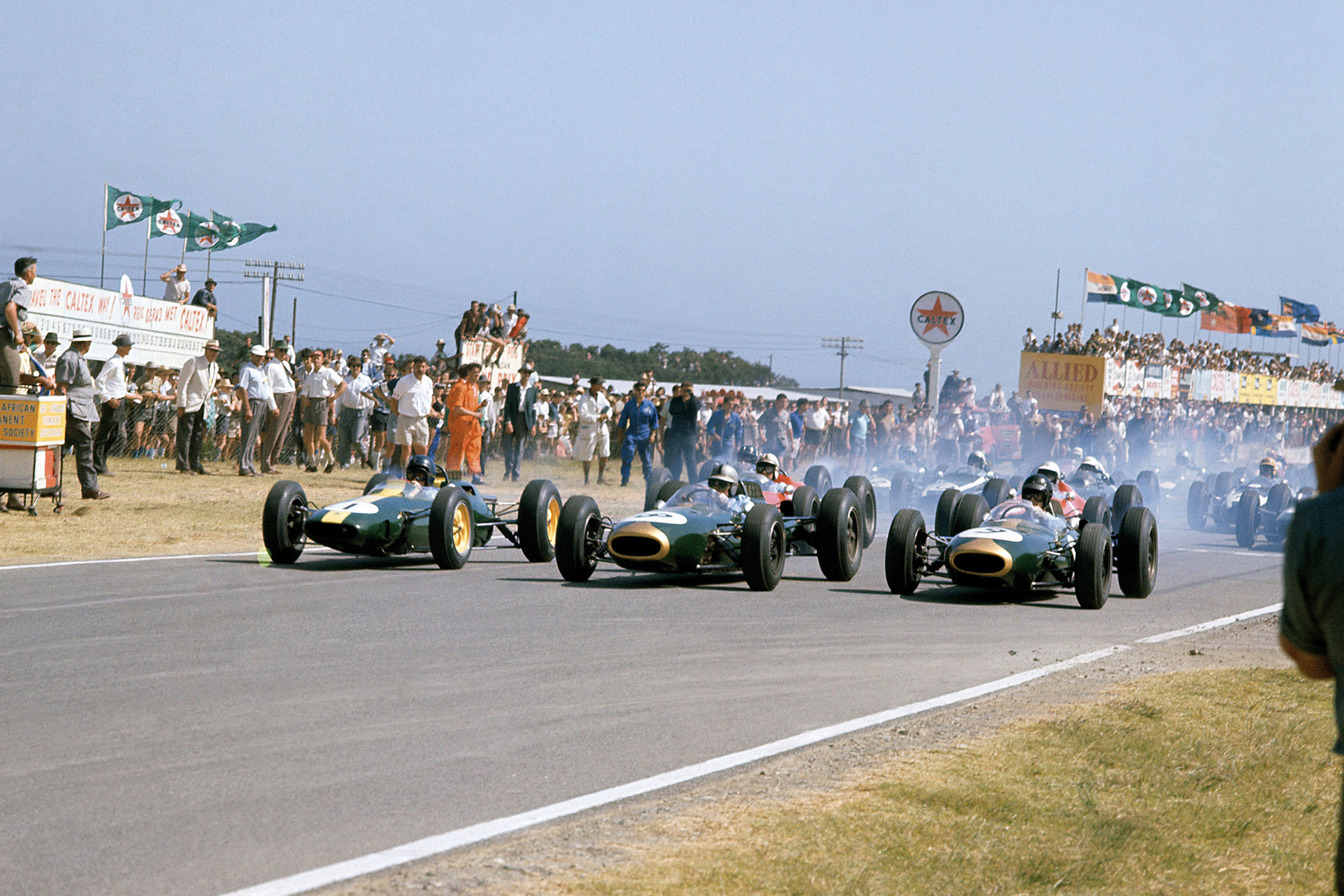 Jim Clark (Lotus 25-Climax), Jack Brabham (Brabham BT7-Climax) and Dan Gurney (Brabham BT7-Climax) lead off the front row of the grid at the start.