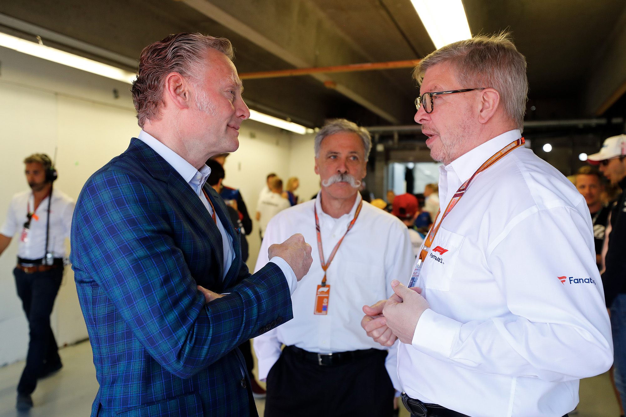 Sean Bratches speaks with Ross Brawn and Chase Carey in an F1 pit