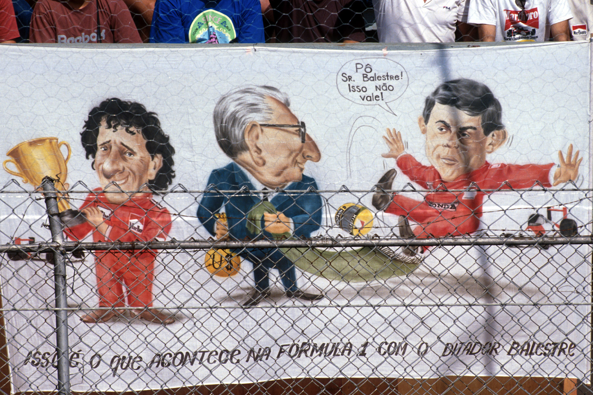 Fans at the 1990 Brazilian Grand Prix hang a banner showing Jean Marie Balestre pulling the rug from under Ayrton Senna