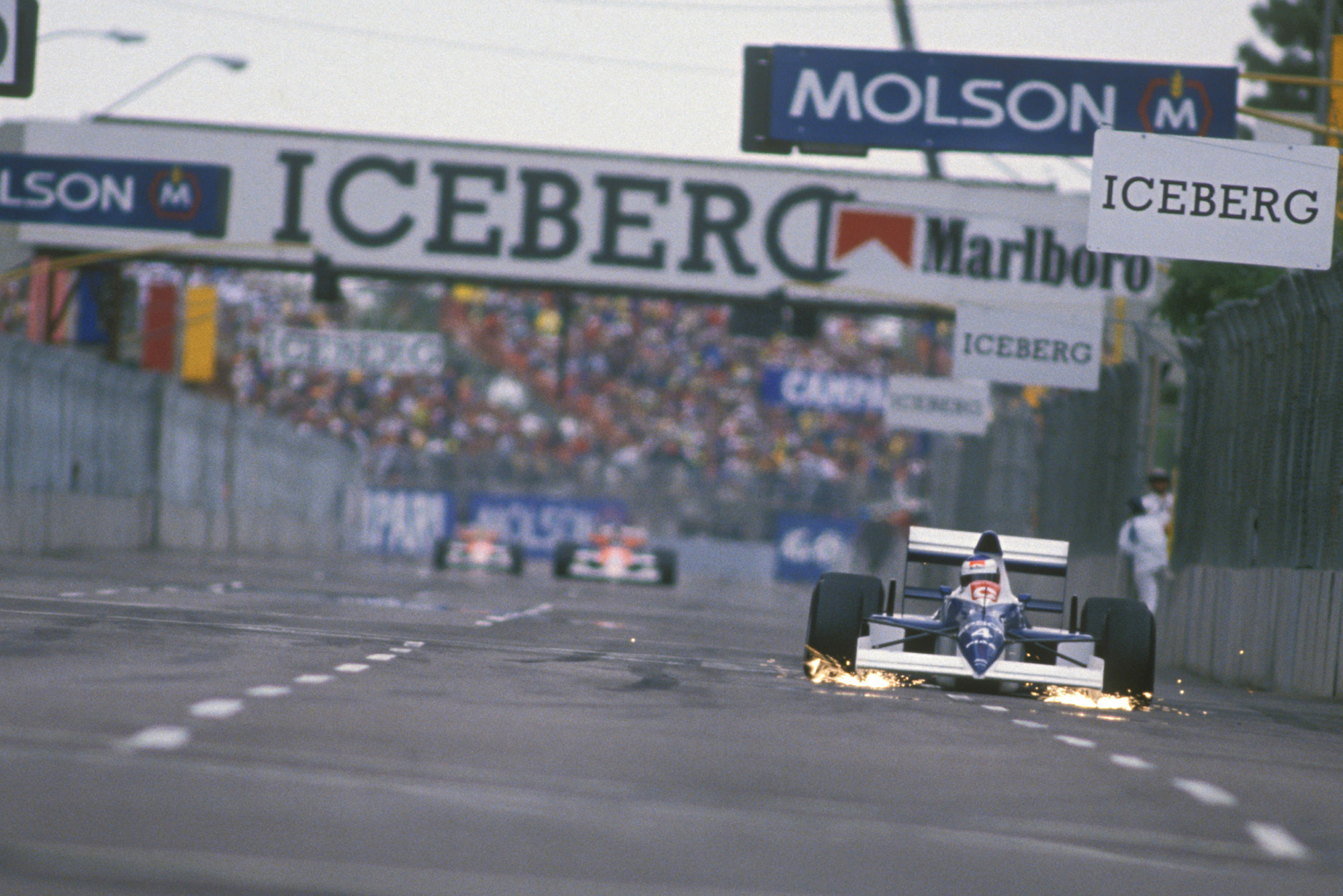 Jean Alesi's Tyrrell leads with a large gap to the chasing McLarens at the 1990 US Grand Prix