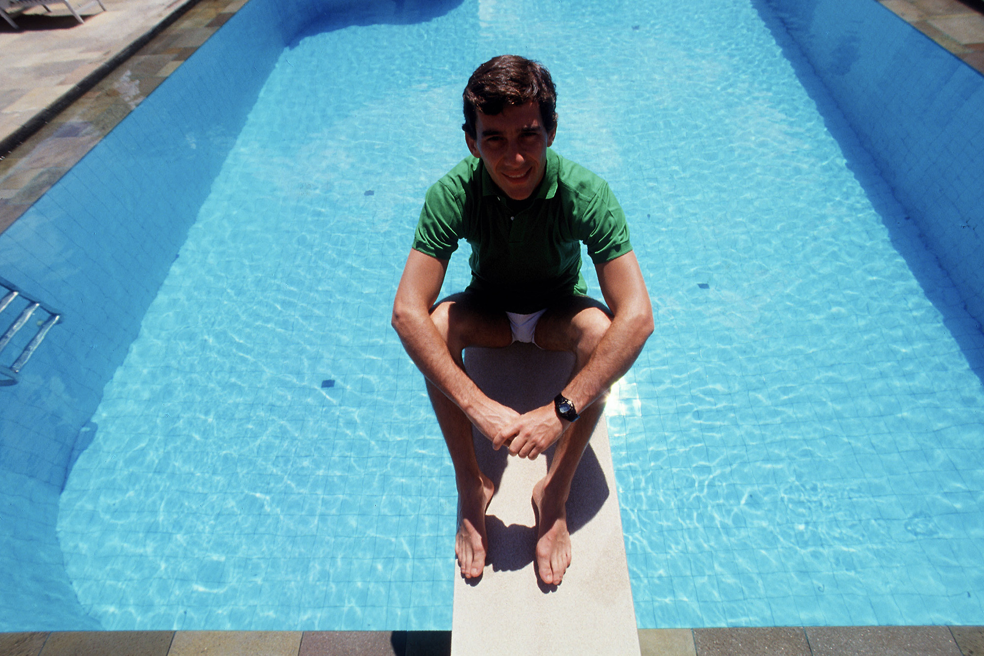 Ayrton Senna sits on the diving board of his home swimming pool