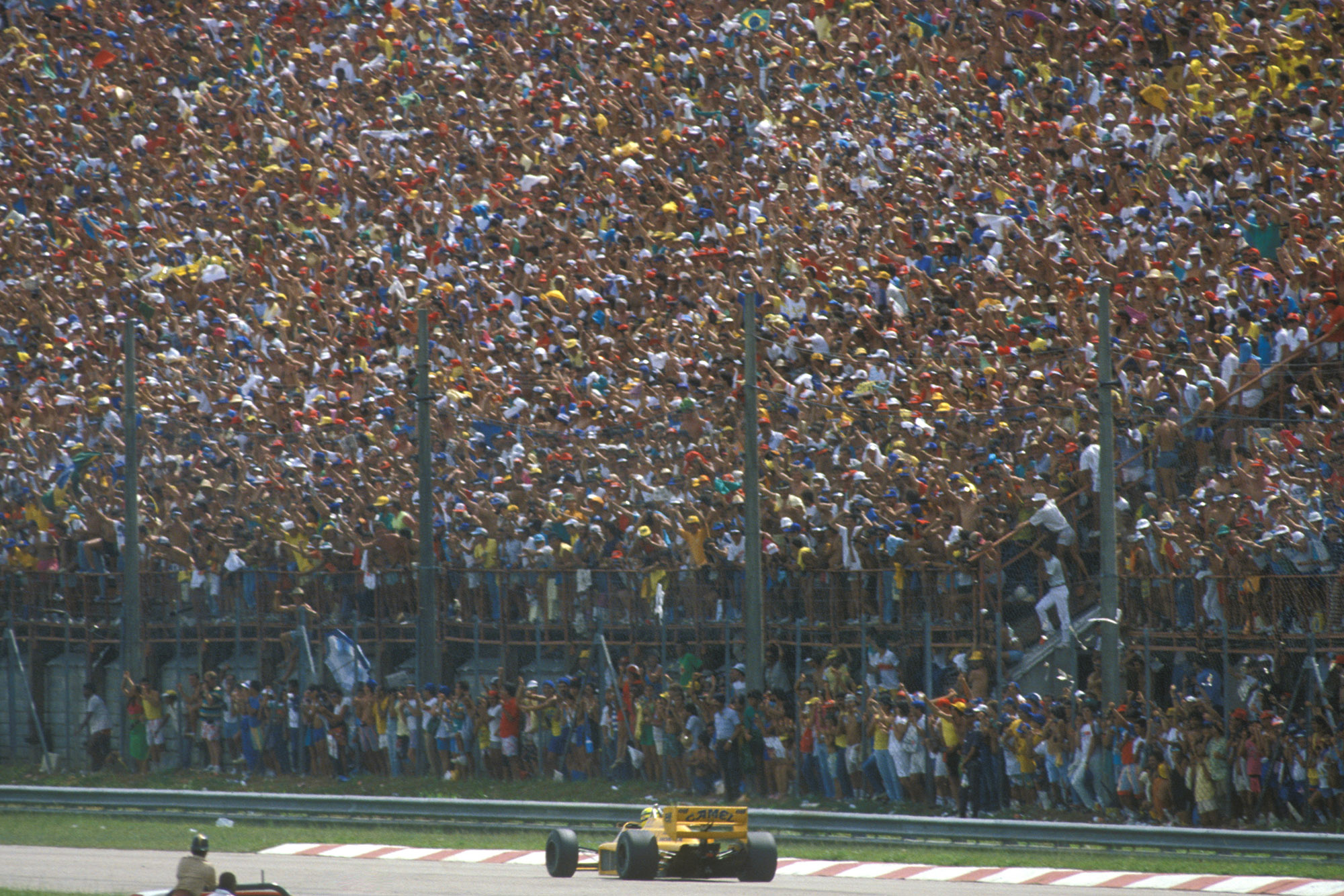 Ayrton Senna drives in front of a packed grandstand of fans at the 1987 Brazilian Grand Prix