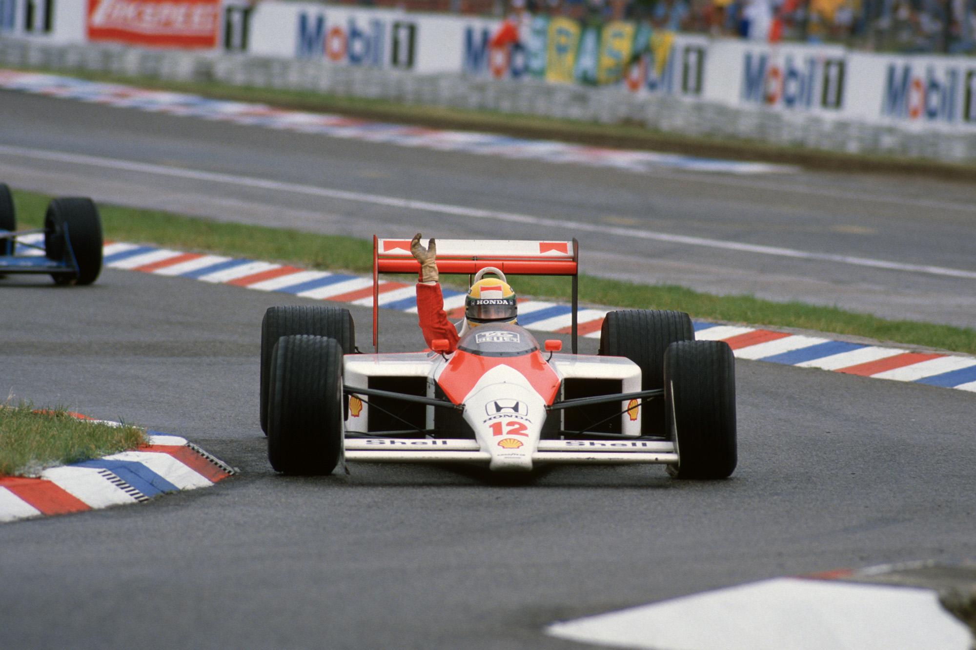 Ayrton Senna waves to fans from his McLaren Honda after winning the 1988 German Grand Prix