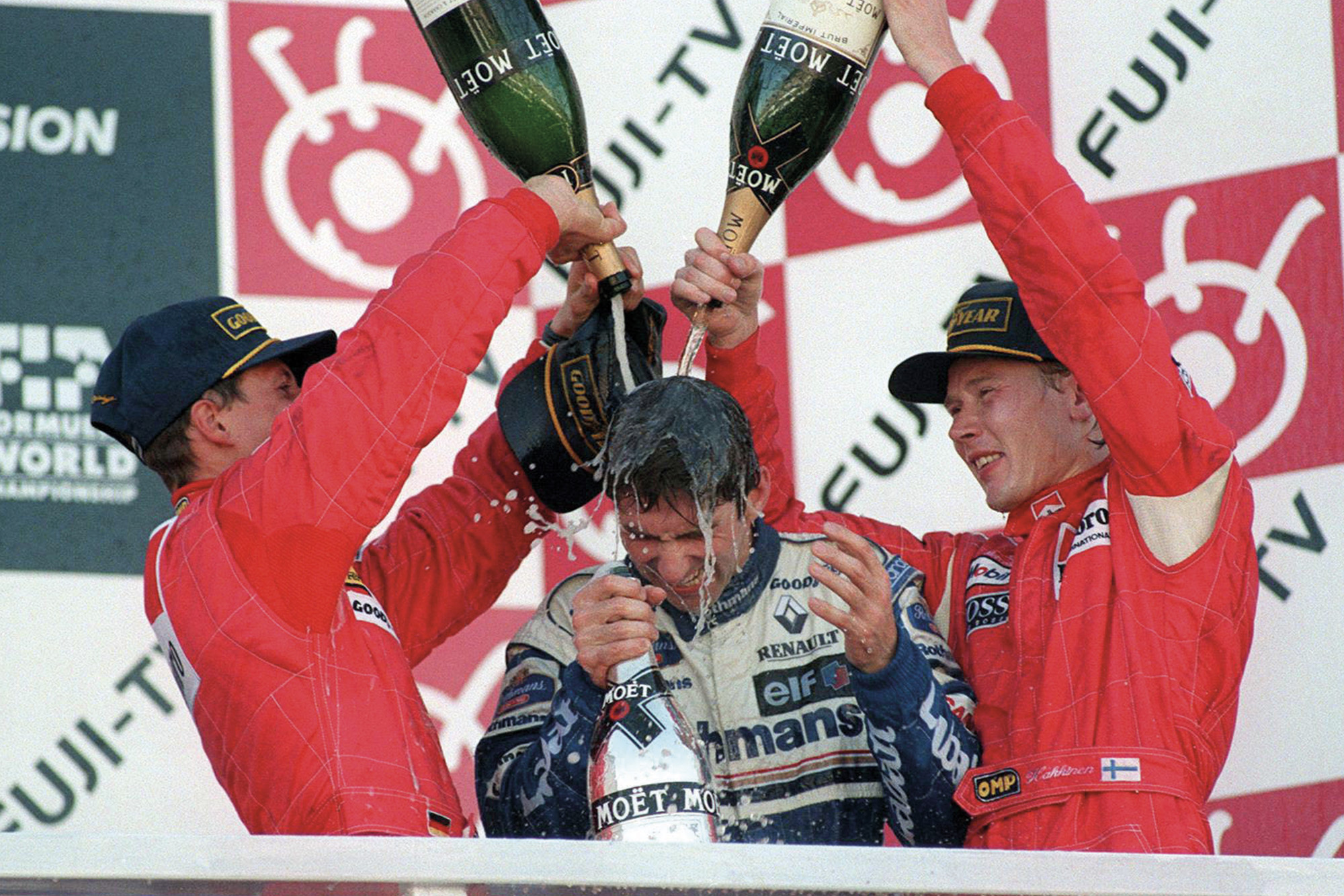 Damon Hill drenched in champagne by Michael Schumacher and Mika Hakkinen after winning the 1996 F1 championship