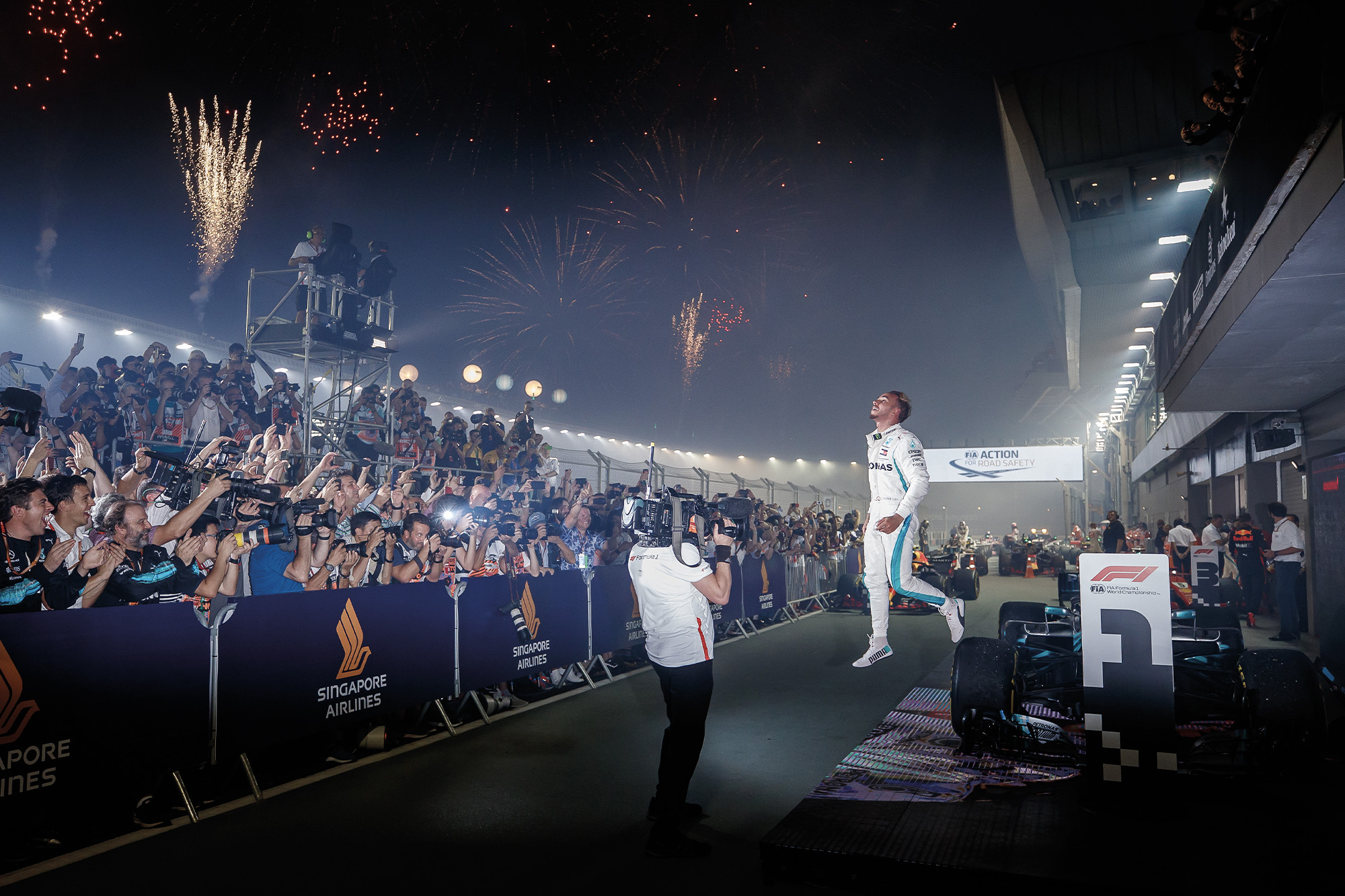 Hamilton leaps off his car after victory in Singapore