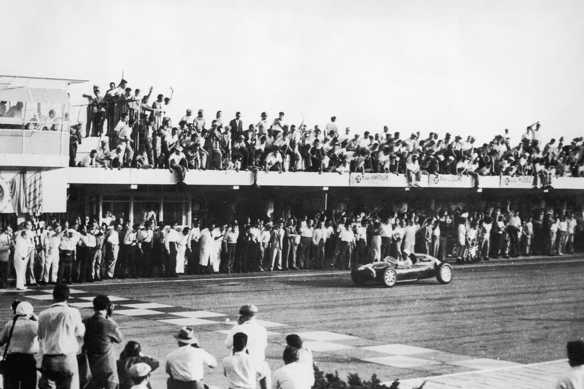 Stirling Moss crosses the line in Buenos Aires to win the 1958 Argentine Grand Prix in a Cooper-Climax T43