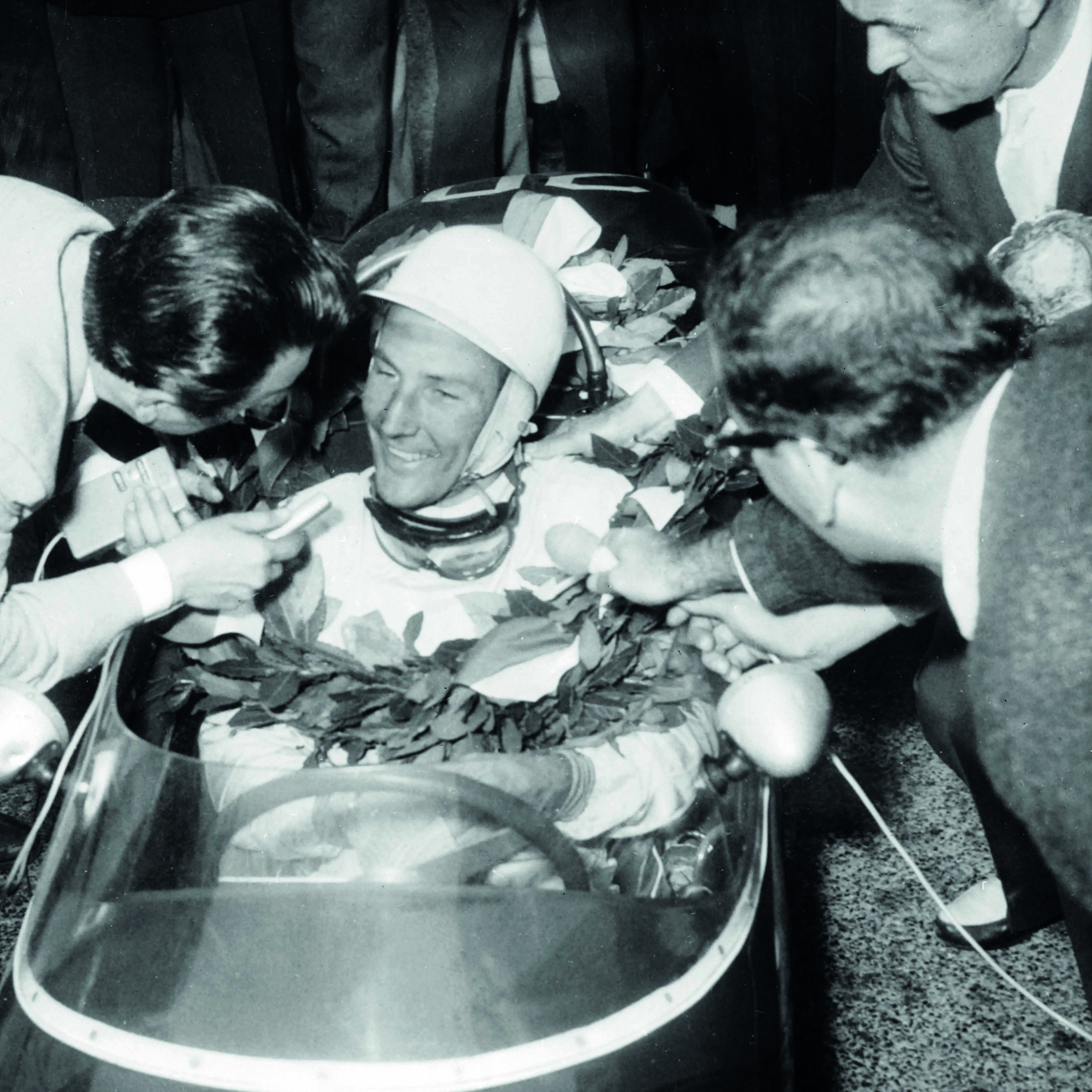 Stirling-Moss-in-his-car-surrounded-by-reporters-after-winning-the-1961-Monaco-Grand-Prix