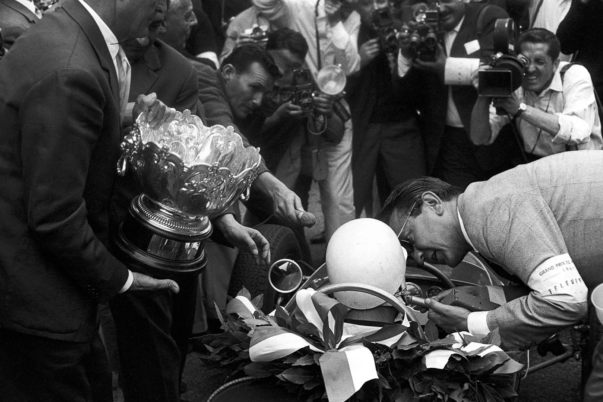 A reporter speaks to Stirling Moss in his Lotus after winning the 1961 Monaco Grand Prix