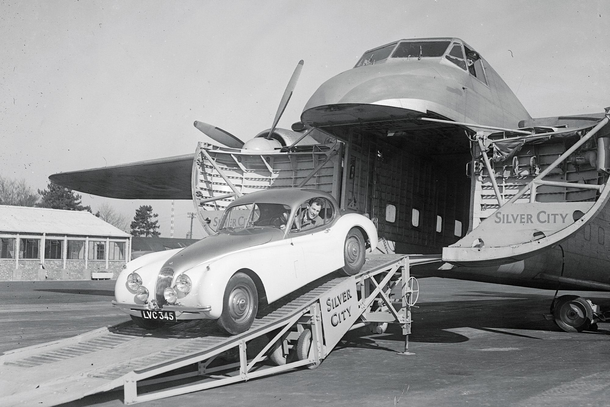 Stirling Moss drives a Jaguar XK120 out of the nose of a cargo plane