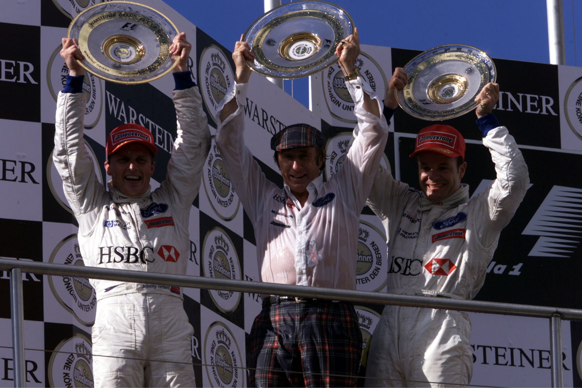 Johnny Herbert Jackie Stewart and Rubens BArrichello on the podium after the 1999 European Grand Prix at the Nurburgring