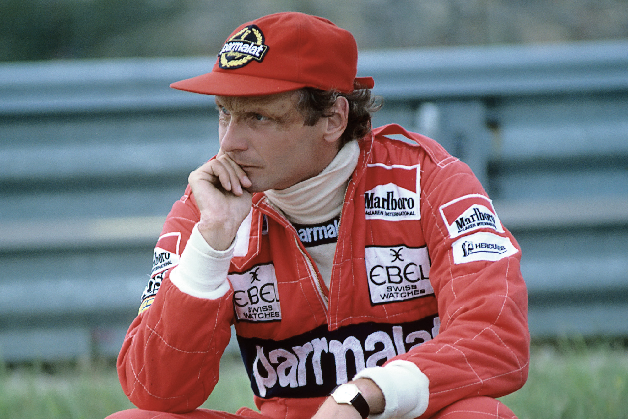 Niki Lauda at the side of the track resting his chin on his hand at the 1982 Dutch Grand Prix