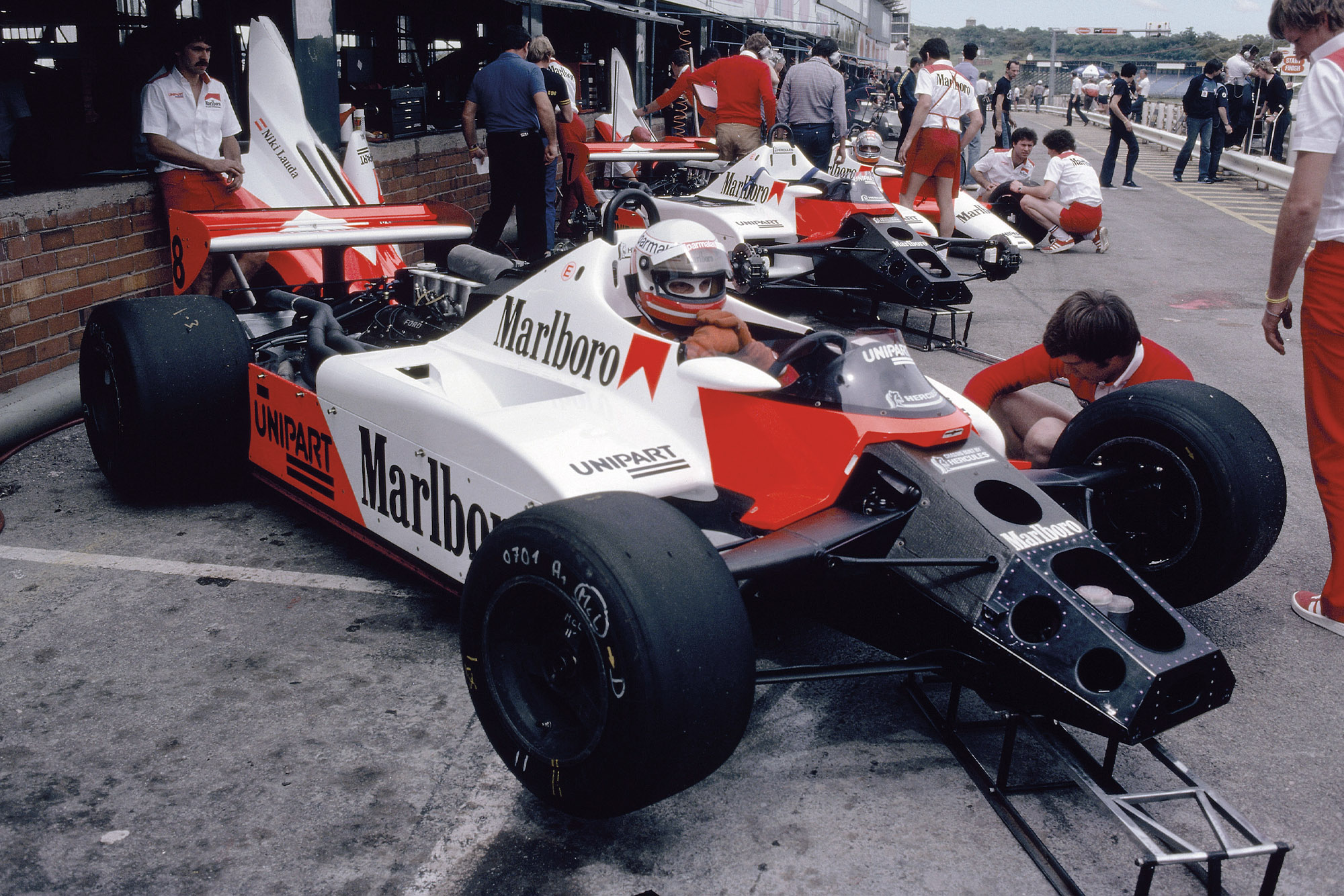 Niki Lauda sits in his McLaren in the pits at Kyalami during the 1982 South African Grand Prix weekend