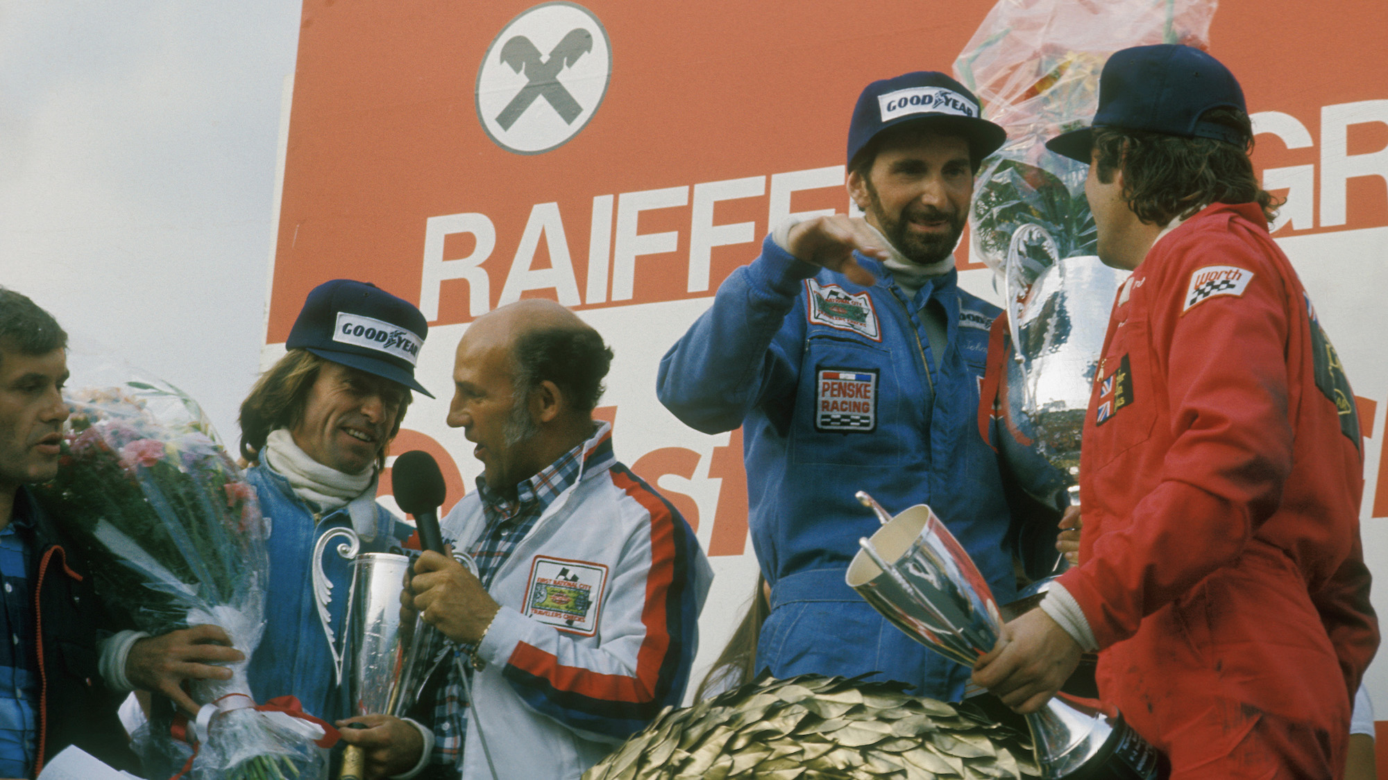 John Watson on the podium after winning at the Osterreichring in the 1976 Austrian Grand Prix