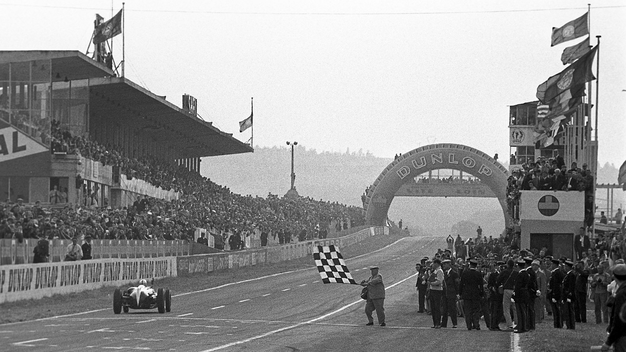 Jack Brabham takes the chequered flag to win in the 1960 French Grand Prix at Reims