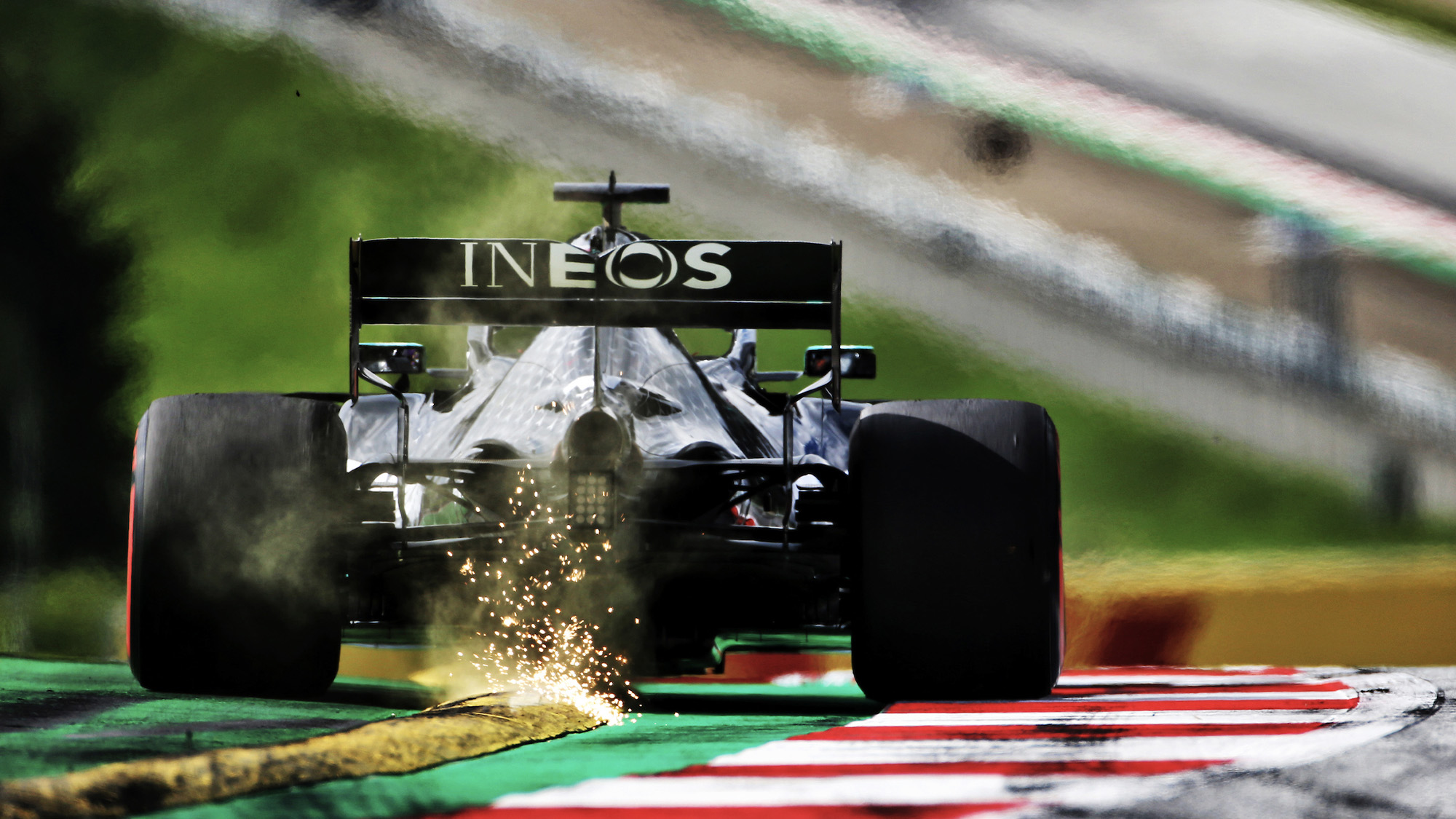 Sparks fly as Lewis Hamilton drives over a yellow kerb ahead of the 2020 F1 Austrian Grand Prix