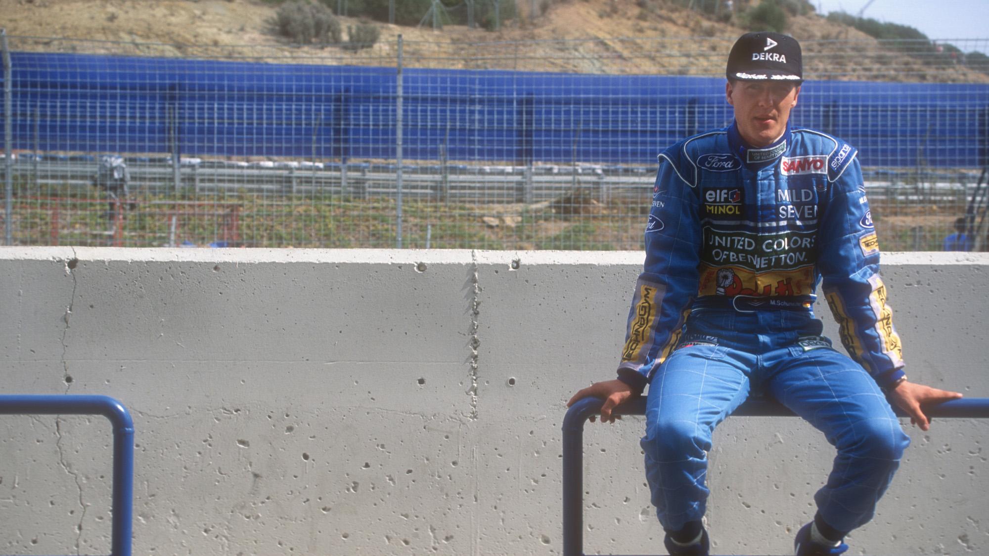 Michael Schumacher sits on a barrier