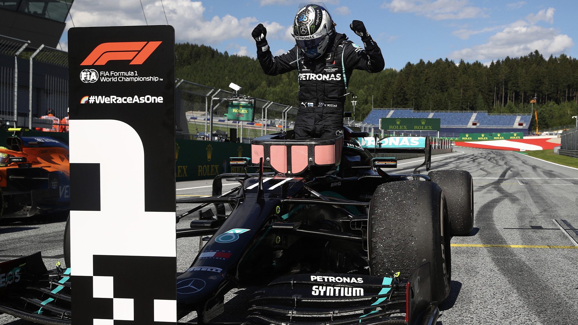Valtteri Bottas holds his arms in the air as he steps out of his car after winning the 2020 F1 Austrian grand prix