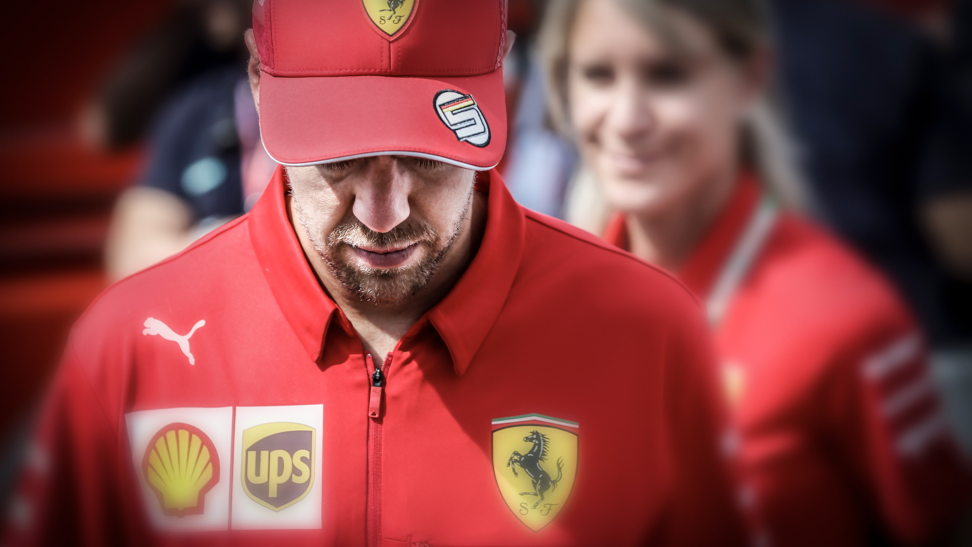 Sebastian Vettel in Ferrari clothing with his head down and cap on