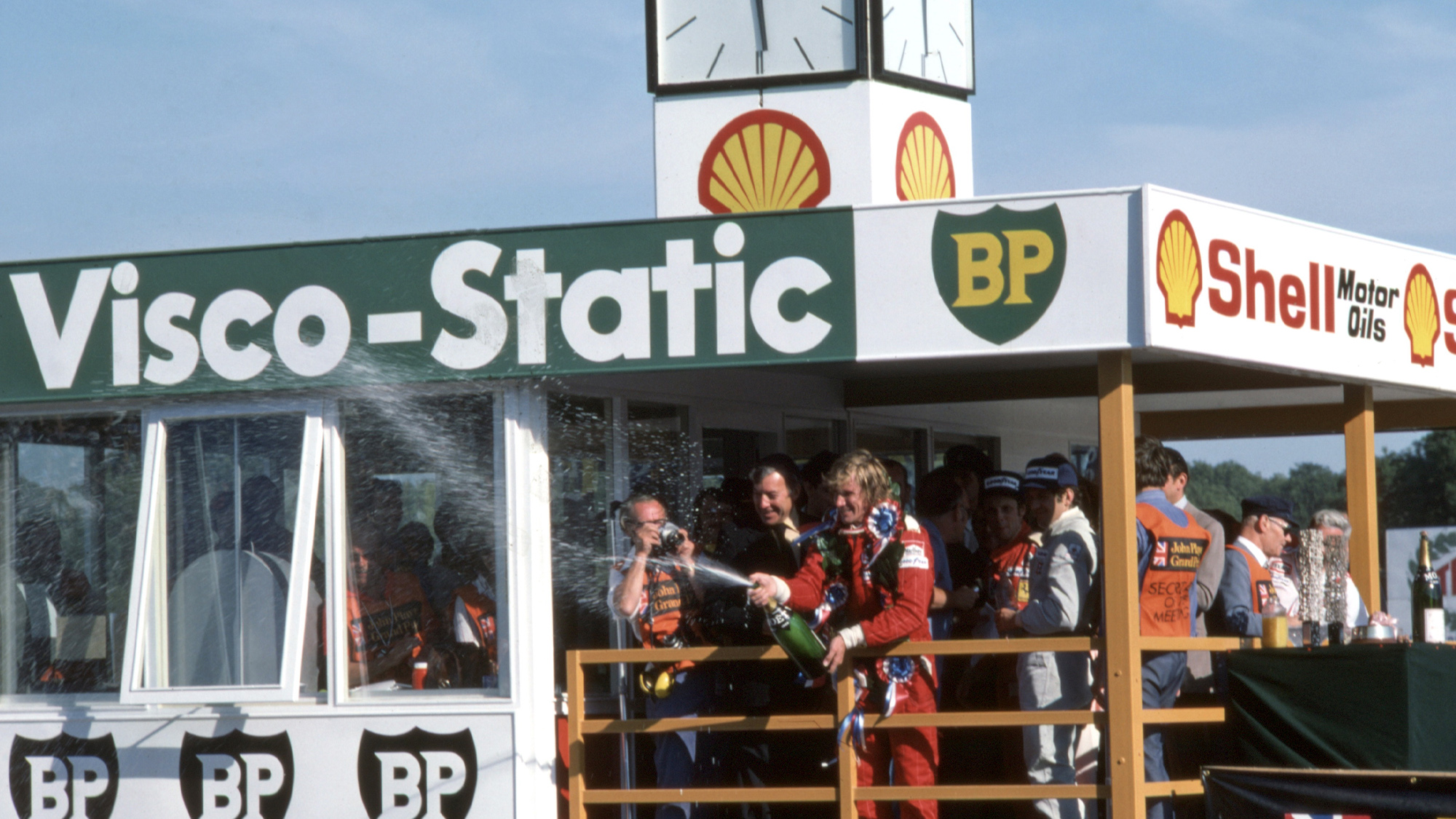 James Hunt sprays champagne on the podium after winning the 1976 British Grand Prix at Brands Hatch - provisionally