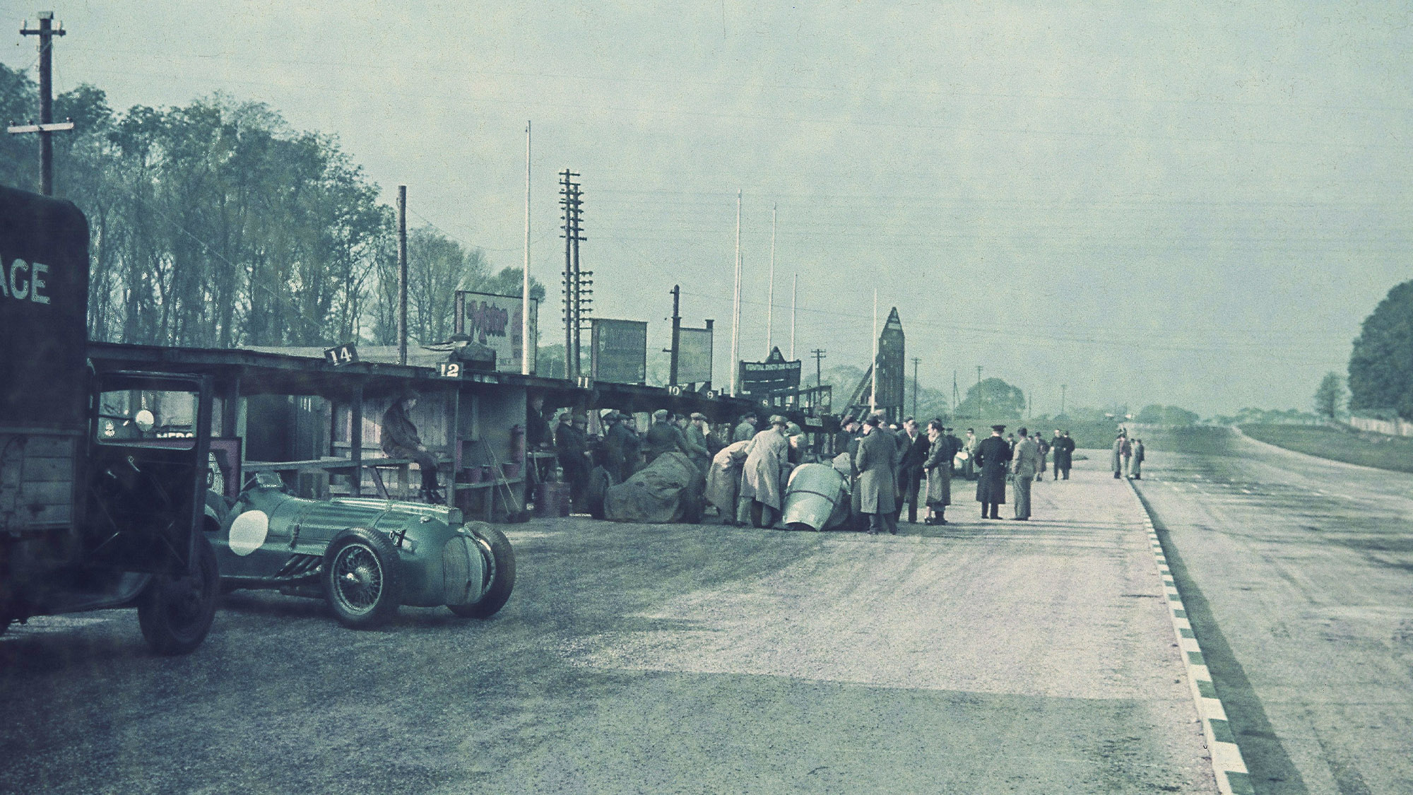 The pitlane ahead of the 1938 Donington Grand Prix with an Ecurie Bleue Delahaye and covered Mercedes W154s