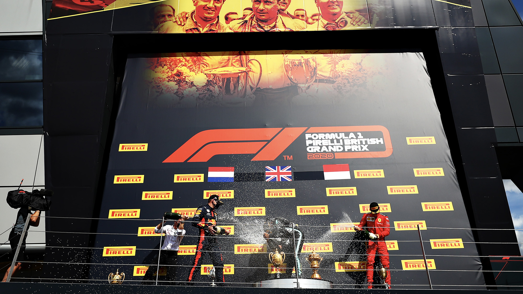 British GP podium celebrations withe Lewis Hamilton Max Verstappen and Charles Leclerc spraying champagne