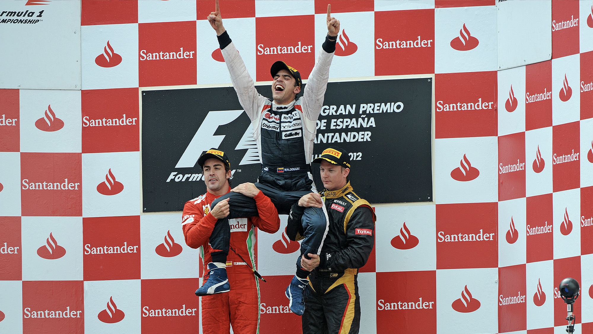Pastor Maldonado is held up by Fernando Alonso and Kimi Raikkonen on the podium after winning the 2012 F1 Spanish Grand Prix
