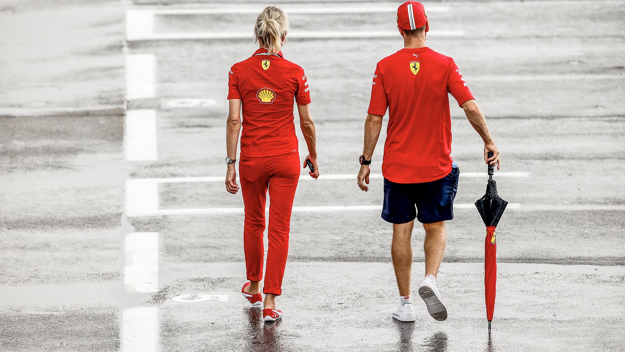 Sebastian Vettel walks through a wet paddock with an umbrella at the 2012 F1 Spanish Grand Prix