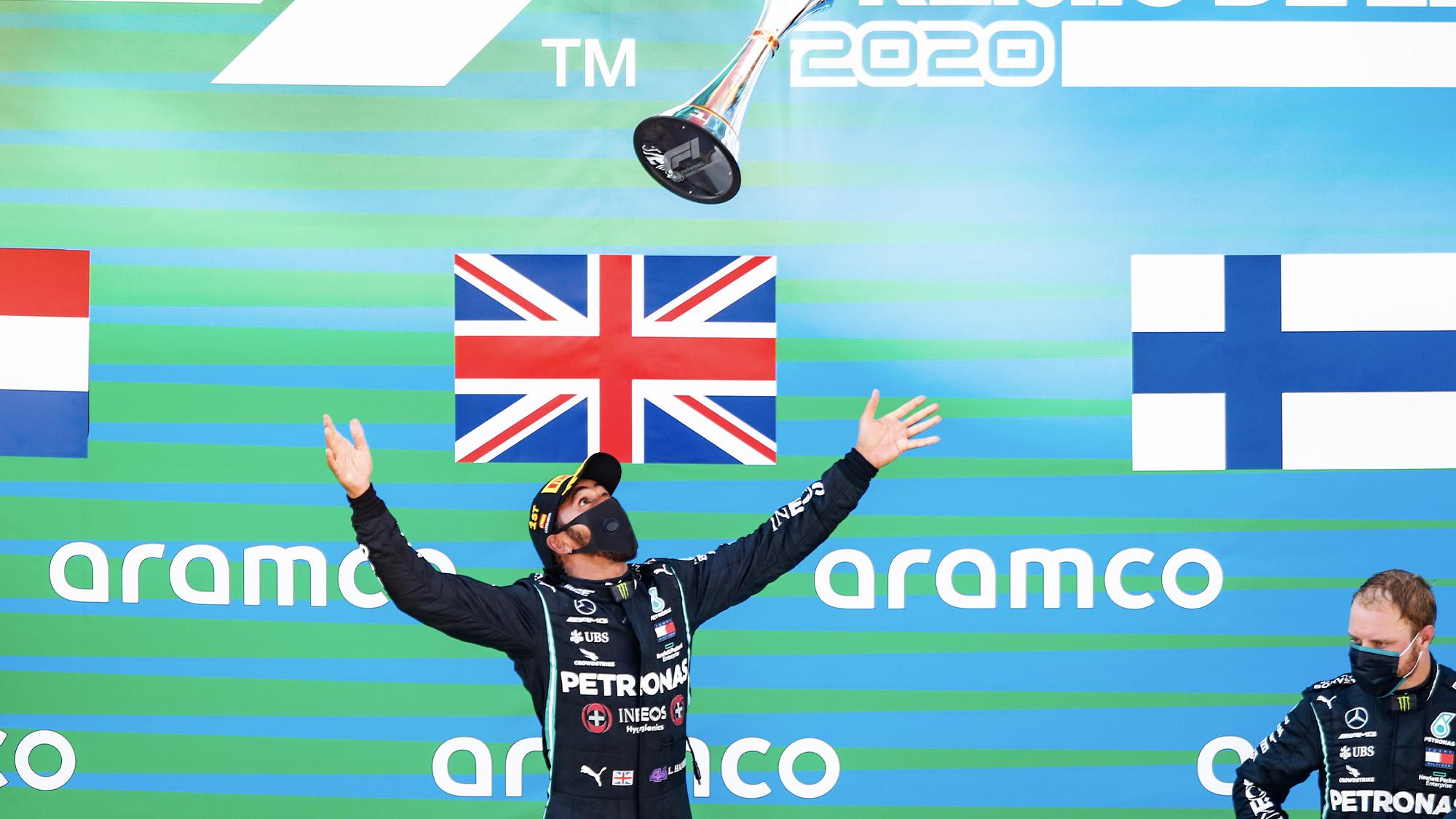 Hamilton throws trophy in the air