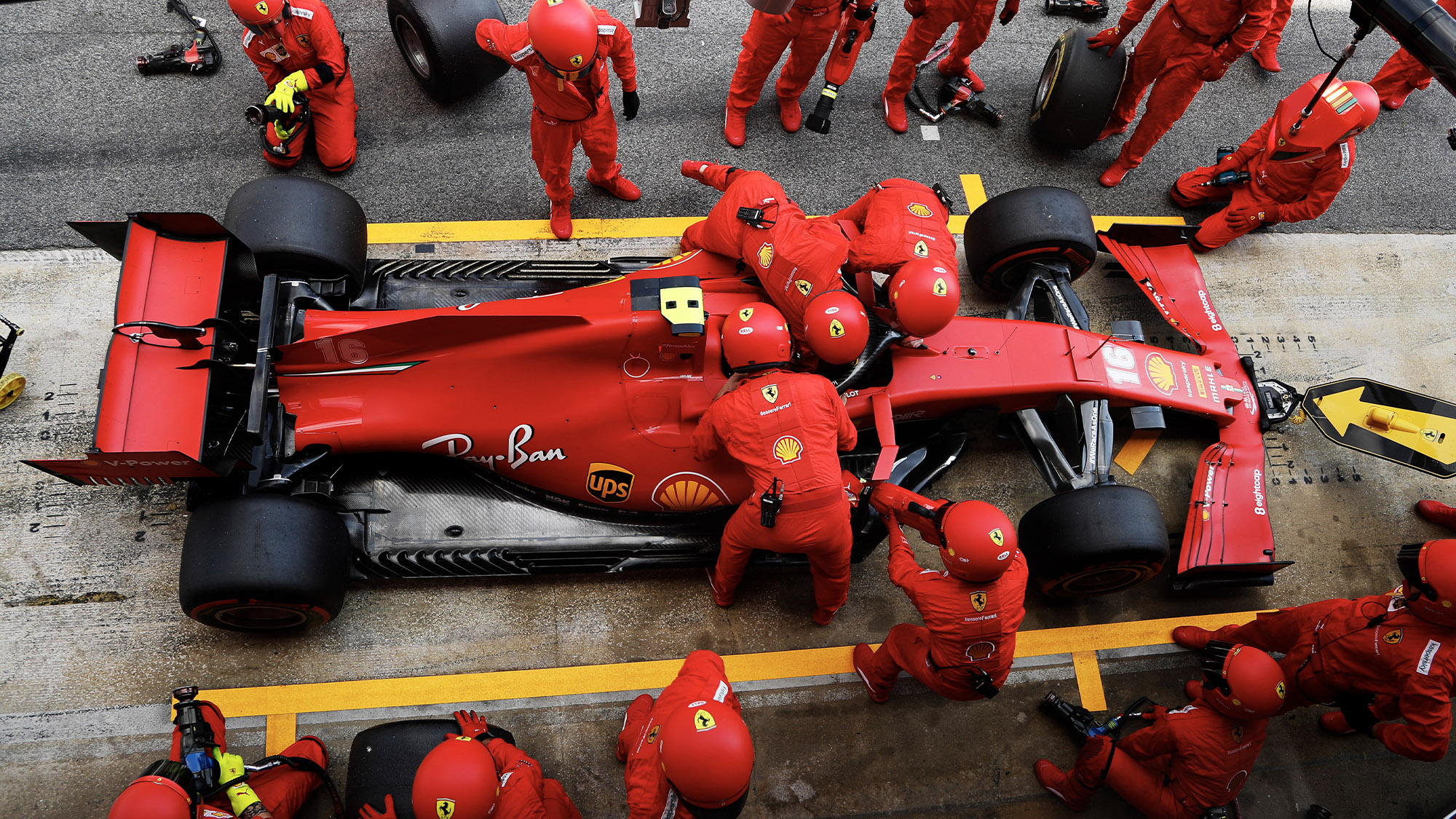 Mechanics fasten Charles Leclerc's seatbelts in the pits at the 2020 f1 Spanish Grand Prix