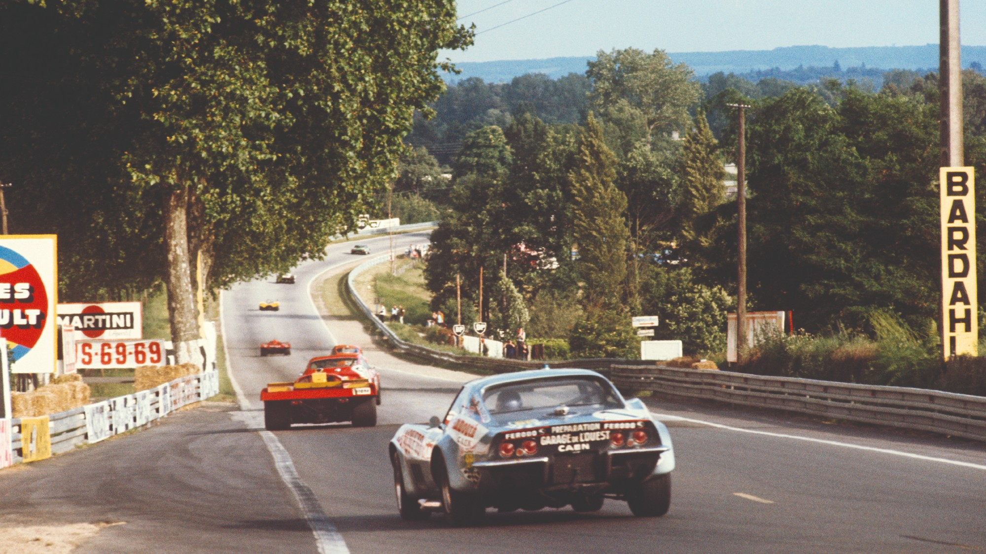 A Chevrolet Corvette follows a Ferarri 512M out of Tertre Rouge and on to the Mulsanne Straight in the 1971 Le Mans 24 Hours race
