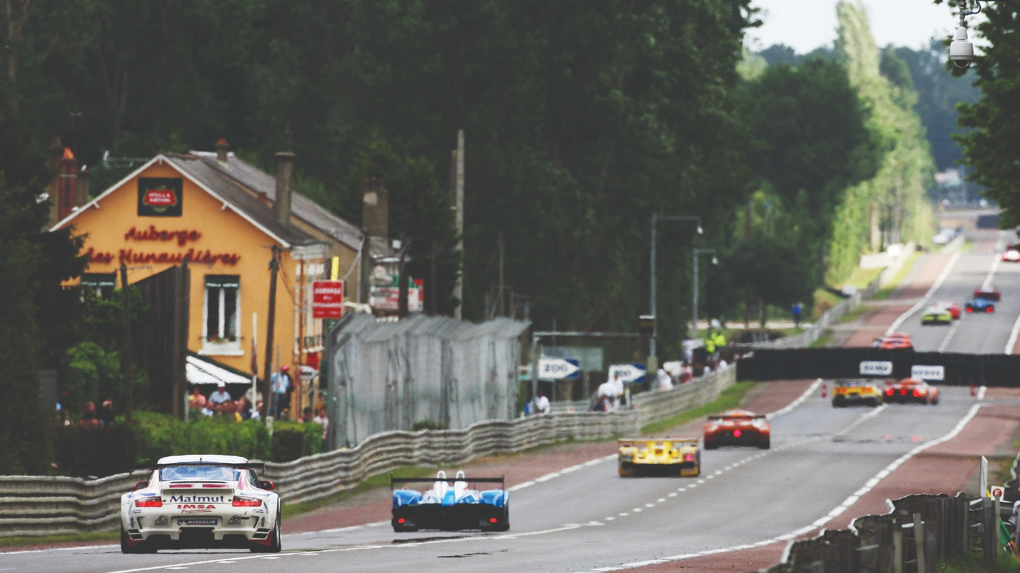 Cars race past the Auberge de Hunaudiere on the Mulsanne Straight duting the 2007 Le Mans 24 Hours