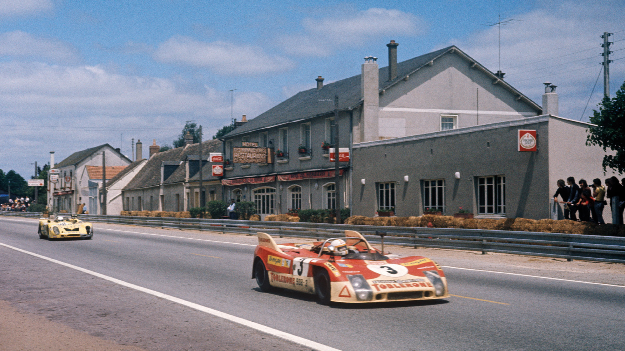 The Juan Fernandez Bernard Cheneviere and Francisco Torredemer Porsche 908 drives past the Hotel Les Hunaudieres in the 1973 Le Mans 24 hours