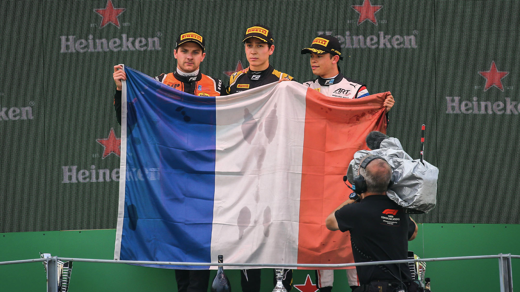 Jack Aitken Jordan king and Nyck de vries raise the french flag in tribute to Anthoine Hubert after a Formula 2 race at Monza in 2019