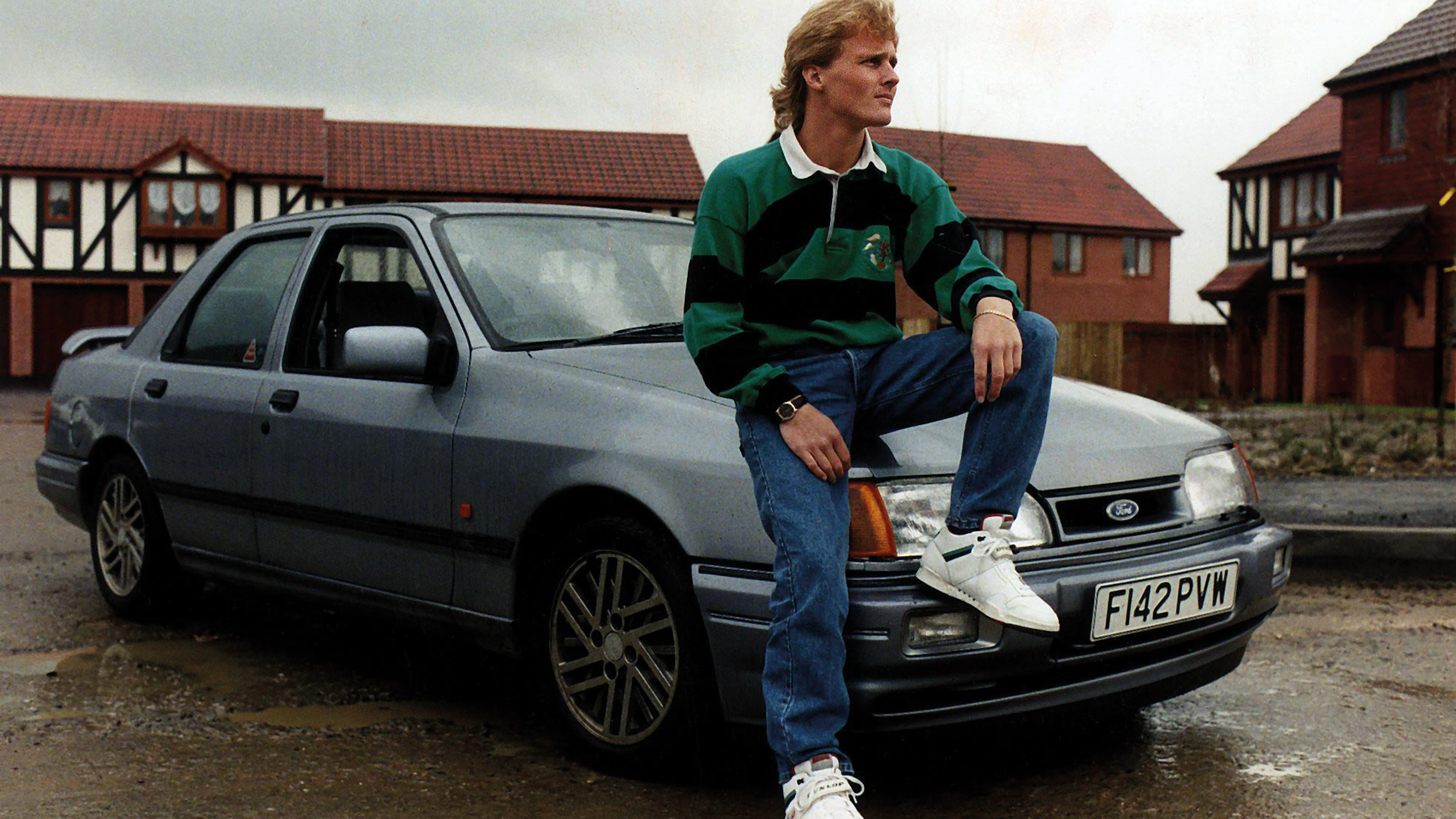 Johnny Herbert sits on the bonnet of a Ford Sierra