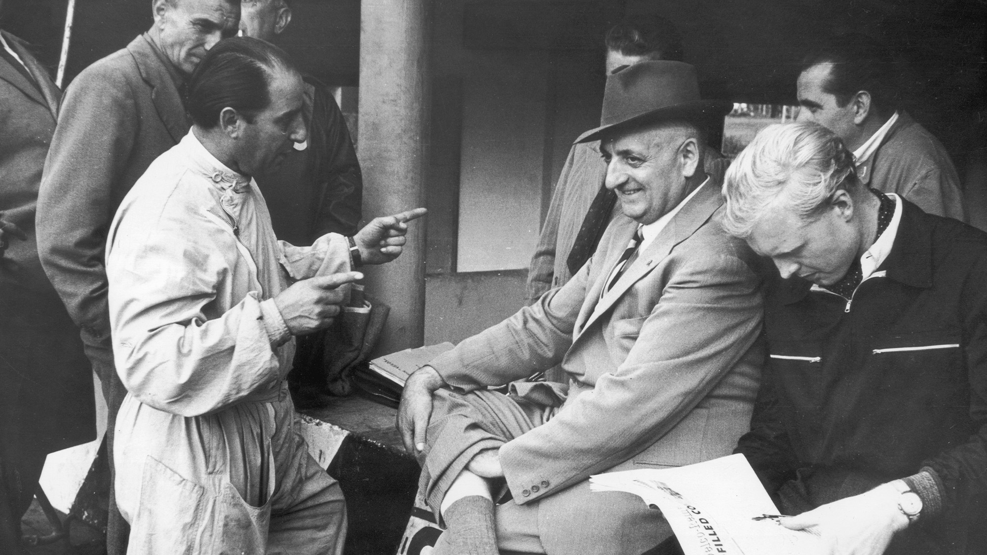 Alberto Ascari speaks with Enzo at Monza, while Mike Hawthorn reads alongside