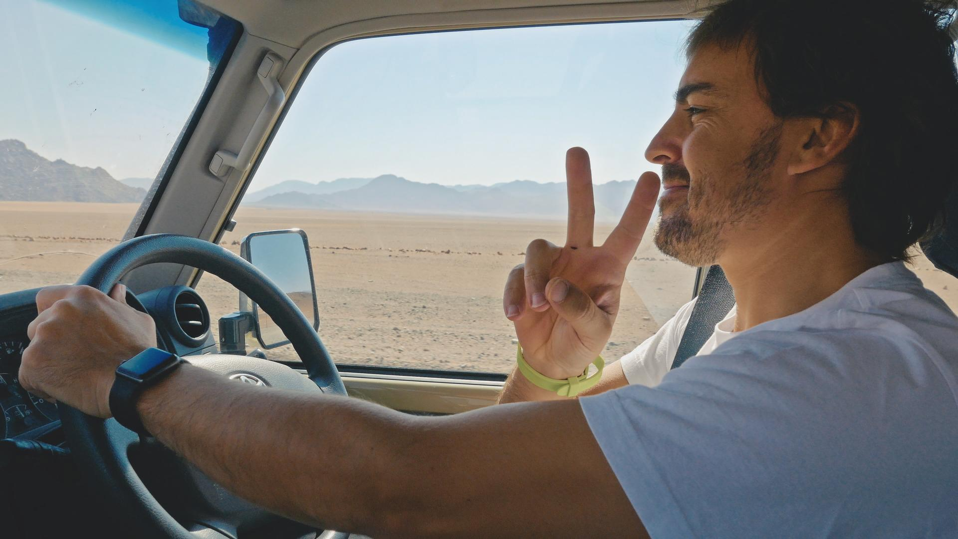 Fernando Alonso gives a V for victory sign as he drives in the desert