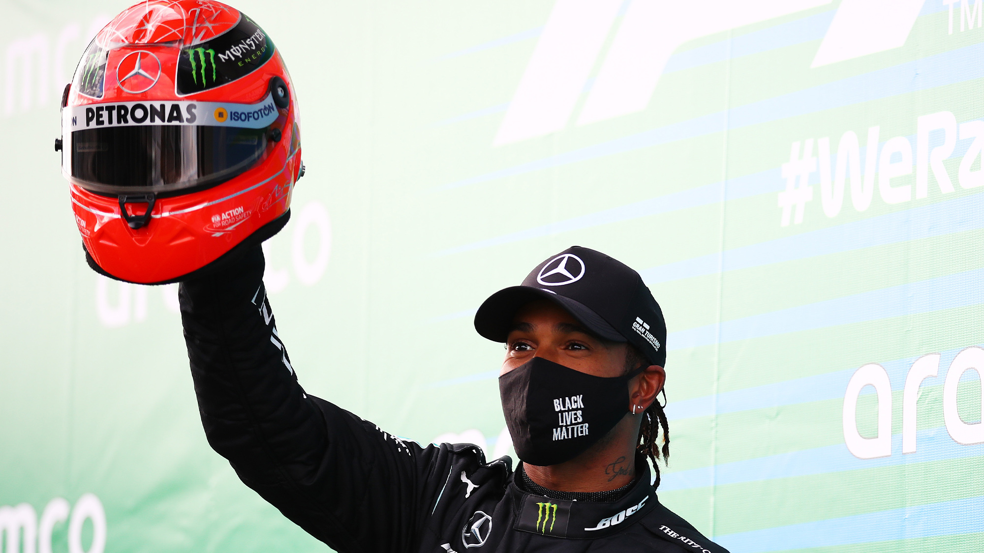 Lewis Hamilton holds a Michael Schumachr helmet in the air after equaling his record F1 wins at the Nurburgring in the 2020 Eifel Grand Prix